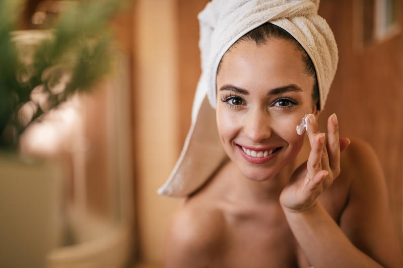Young beautiful woman applying face cream in the bathroom.