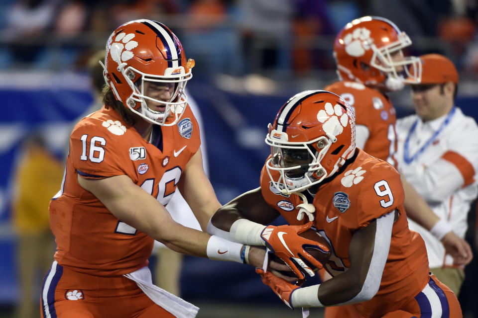 Clemson quarterback Trevor Lawrence (16) hands off to Clemson running back Travis Etienne (9) during warmups prior to the Atlantic Coast Conference championship NCAA college football game between against Virginia in Charlotte, N.C., Saturday, Dec. 7, 2019. (AP Photo/Mike McCarn)