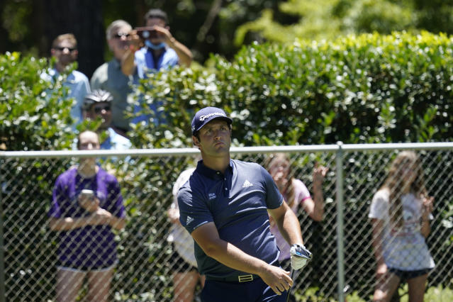 Fans stand behind a fence as Jon Rahm, of Spain, watches his tee shot on the second hole during the first round of the Charles Schwab Challenge golf tournament at the Colonial Country Club in Fort Worth, Texas, Thursday, June 11, 2020. (AP Photo/David J. Phillip)