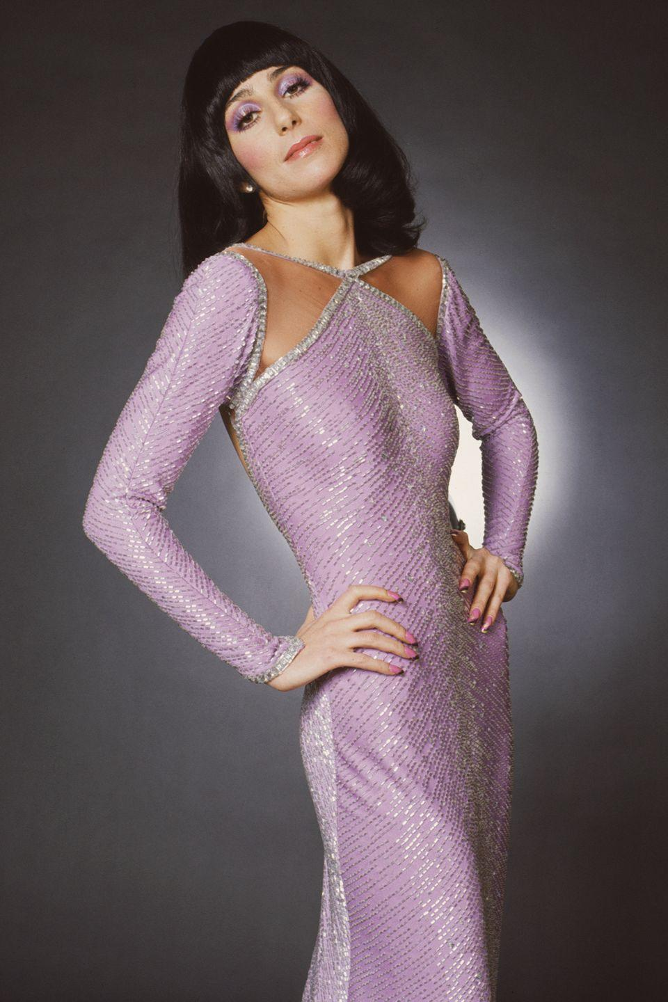 <p>She poses for a photo in a sparkly, purple gown.</p>