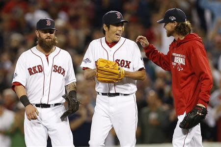 Oct 5, 2013; Boston, MA, USA; Boston Red Sox first baseman Mike Napoli (12) celebrates with pitcher Koji Uehara (19) and pitcher Clay Buchholz (11) after defeating the Tampa Bay Rays 7-4 in game two of the American League divisional series playoff baseball game at Fenway Park. Mandatory Credit: Greg M. Cooper-USA TODAY Sports