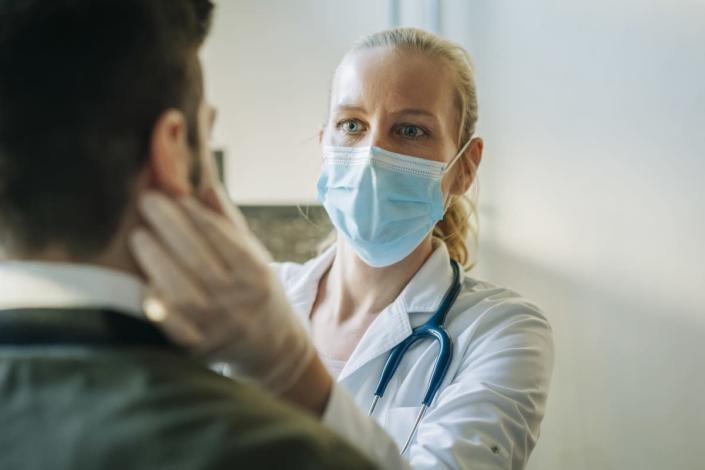 Female doctor wearing surgical mask examining infected patient. Mature healthcare worker checking mid adult man. They are at pharmacy.