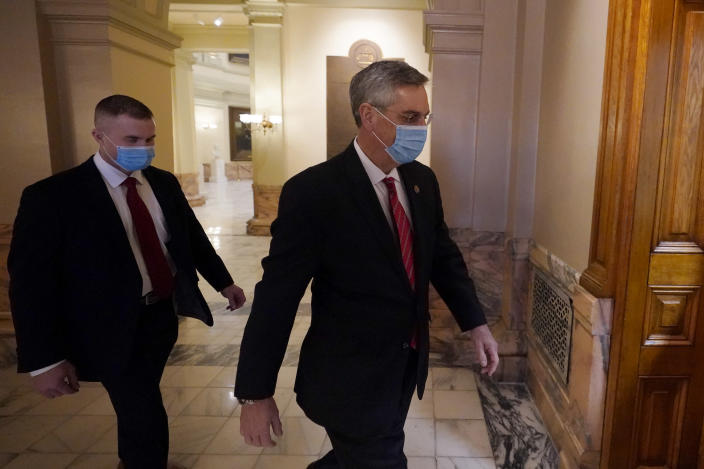 Georgia Secretary of State Brad Raffensperger, right, walks to his office in the Capitol Building Monday, Jan. 4, 2021, in Atlanta. (AP Photo/John Bazemore)