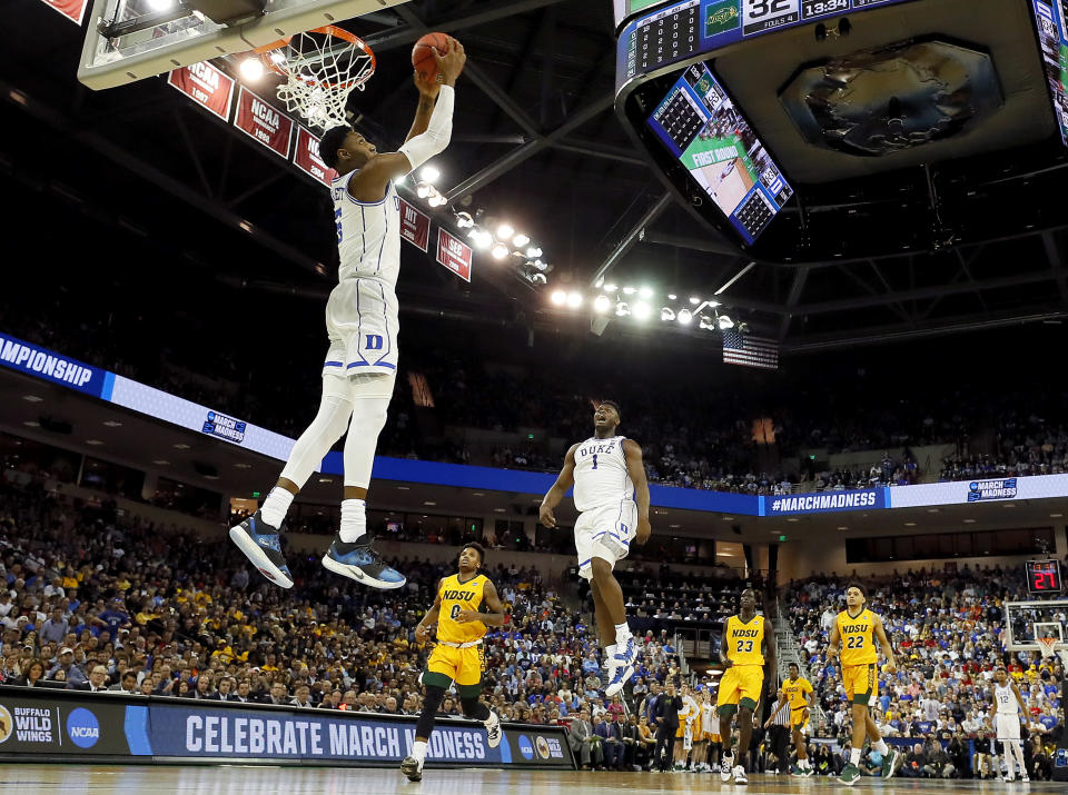 <p>RJ Barrett #5 of the Duke Blue Devils dunks the ball as teammate Zion Williamson #1 celebrates against the North Dakota State Bison in the second half during the first round of the 2019 NCAA Men's Basketball Tournament at Colonial Life Arena on March 22, 2019 in Columbia, South Carolina. (Photo by Kevin C. Cox/Getty Images) </p>