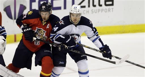 Florida Panthers' Tomas Kopecky (82) and Winnipeg Jets' Grant Clitsome (24) jostle for position near the goal during the first period of an NHL hockey game in Sunrise, Fla., Tuesday, March 5, 2013. (AP Photo/J Pat Carter)