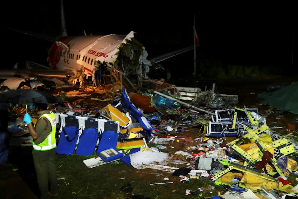 A security personnel stands guard in front of the wreckage from an Air India Express jet, which was carrying more than 190 passengers and crew from Dubai, after it crashed at Calicut International Airport in Karipur, Kerala, early on August 8, 2020. - At least 17 people were killed on August 7 when a passenger jet was ripped in two after it overshot and skidded off the runway upon landing in southern India, officials said. (Photo by Arunchandra BOSE / AFP) (Photo by ARUNCHANDRA BOSE/AFP via Getty Images)