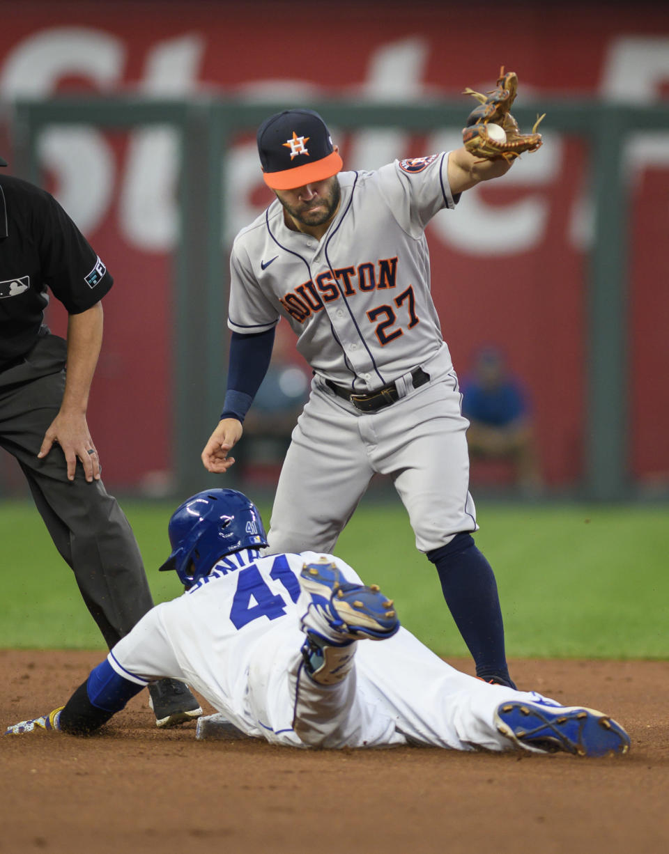 Kansas City Royals' Carlos Santana (41) is safe on a double under the throw to Houston Astros second baseman Jose Altuve (27) during the first inning of a baseball game Tuesday, Aug. 17, 2021, in Kansas City, Mo. (AP Photo/Reed Hoffmann)