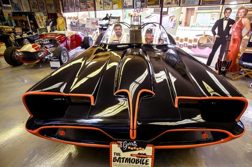 """NORTH HOLLYWOOD, CA -JULY 26, 2021: Jared Barris and his mother Joji Barris-Paster are photographed inside an exhibition replica of the Batmobile, on display inside the showroom at Barris Kustom Industries in North Hollywood. The Batmobile was designed exclusively for the 1966 TV show, """"Batman,"""" by the late George Barris, Jared's grandfather, and Joji's father. Barris Kustom Industries is being listed for sale. (Mel Melcon / Los Angeles Times)"""