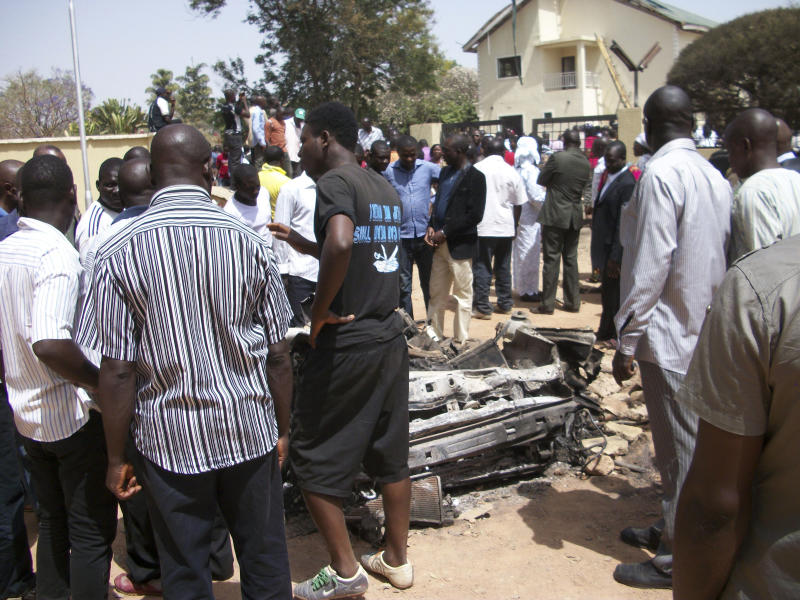 People gather around a car used by a suicide bomber at a catholic church in Jos, Nigeria on Sunday, March 11, 2012. A suspected suicide attack hit a Catholic church in the central Nigerian city of Jos on Sunday, killing three people, the National Emergency Management Agency (NEMA) said. (AP Photos)