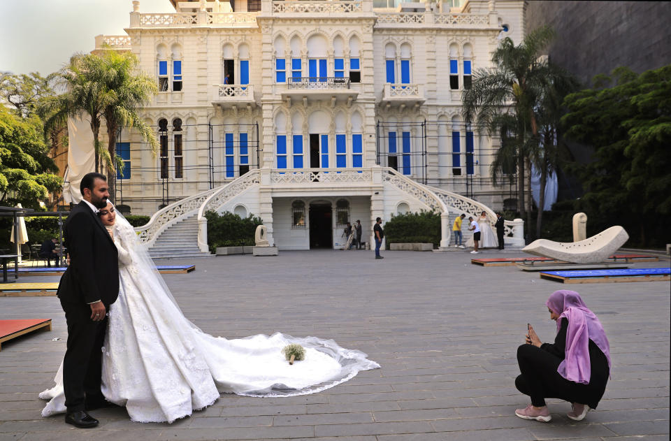 A woman takes pictures of a Lebanese bride and groom in the courtyard of the Sursock Museum, which was damaged in the explosion last August at Beirut's port, in Beirut, Lebanon, Lebanon's only modern art museum, the Sursock, is still rebuilding a year after the explosion decimated it and some hope that reopening it will be a first step in the harder task of rebuilding the city's once thriving arts scene. (AP Photo/Hussein Malla)