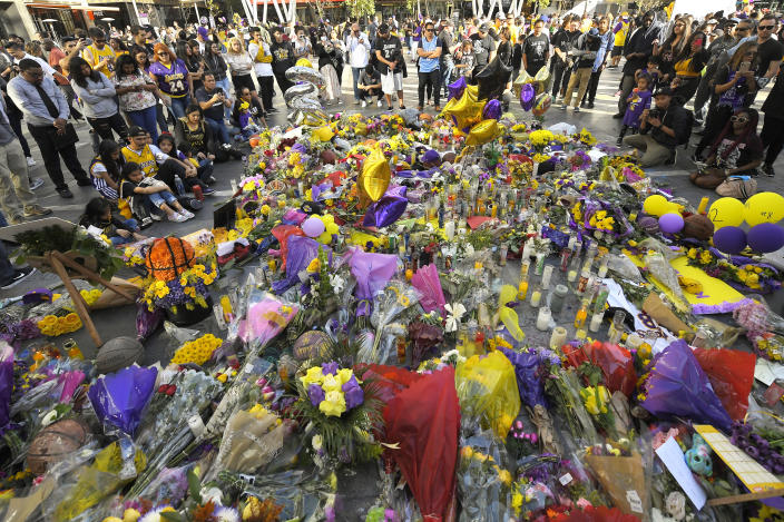 FILE - In this Jan. 28, 2020, fans gather in front of several memorials set up at LA Live, near Staples Center where the Los Angeles Lakers play, to memorialize Kobe Bryant in Los Angeles following a helicopter crash that killed the former NBA basketball player, his 13-year-old daughter, Gianna, and seven others. (AP Photo/Mark J. Terrill, File)