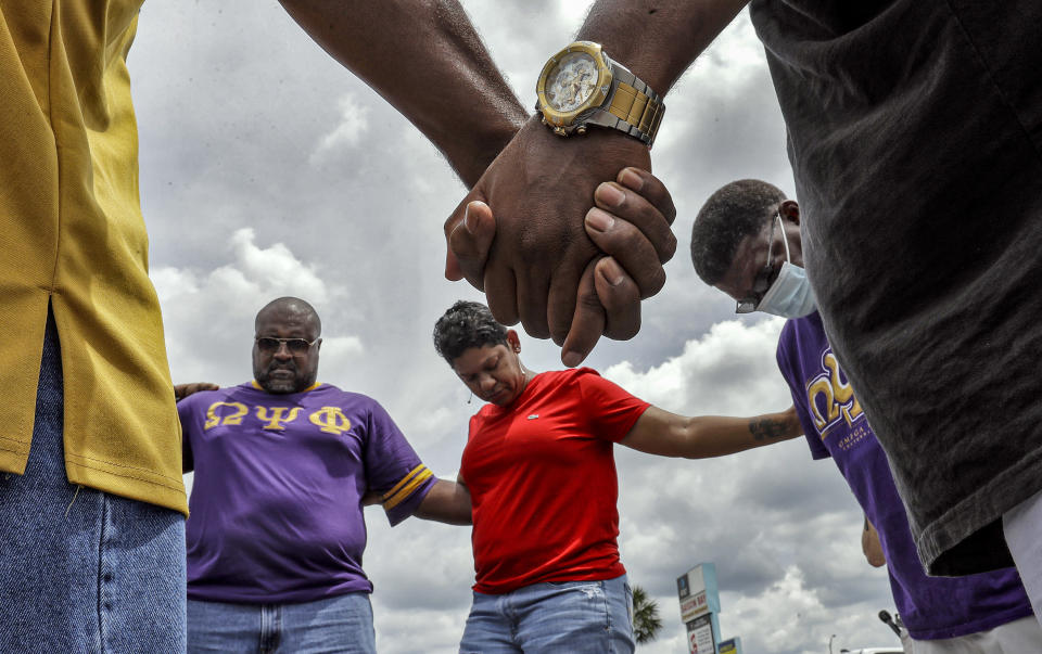 FILE - This photo from Monday June 1, 2020, shows members of the Omega Psi Phi fraternity hold hands in prayer near the site where businesses were destroyed during a night of unrest over the killings of black people by police. The chaos unleashed in 2020, amid the coronavirus pandemic, has created space for different voices to speak, for different conversations to be had and for different questions to be asked. (AP Photo/Chris O'Meara, File)