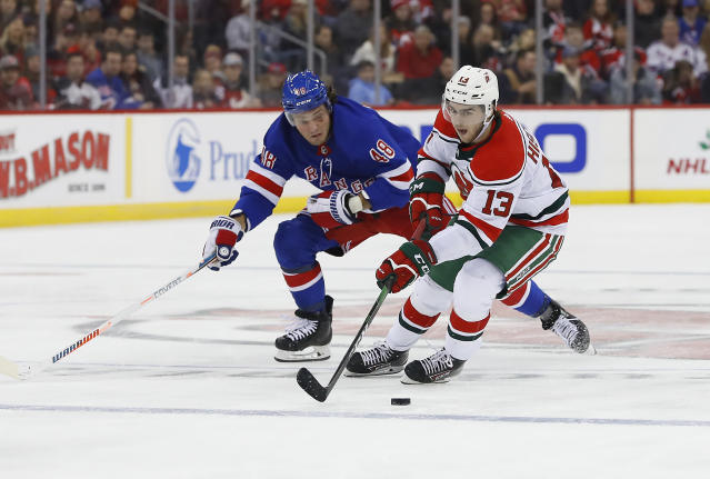 New Jersey Devils center Nico Hischier (13) skates with the puck against New York Rangers left wing Brendan Lemieux (48) during the second period of an NHL hockey game Saturday, Nov. 30, 2019, in Newark,N.J. (AP Photo/Noah K. Murray)