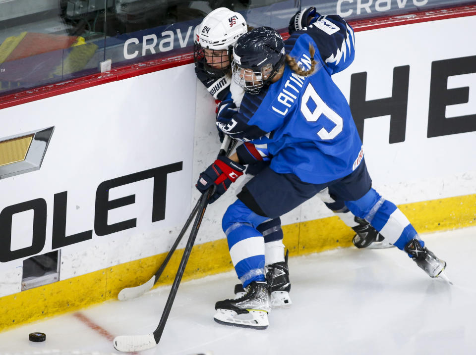 Finland's Nelli Laitinen, right, checks Dani Cameranesi, of the United States, during the second period of an IIHF women's hockey championships semifinal in Calgary, Alberta, Monday, Aug. 30, 2021. (Jeff McIntosh/The Canadian Press via AP)