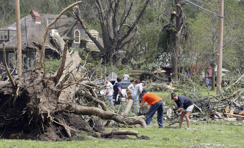 Volunteers and residents help clean up debris Sunday, April 15, 2012, in the aftermath of a tornado which damaged much of Thurman, Iowa on Saturday evening. Fremont County Emergency Management Director Mike Crecelius said about 75 percent of the 250-person town was destroyed. (AP Photo/The Des Moines Register, Mary Chind) NO SALES, NO MAGS, MANDATORY CREDIT