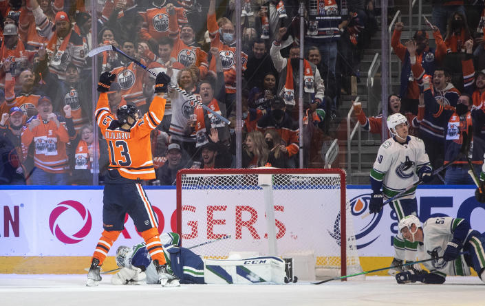 Vancouver Canucks goalie Thatcher Demko, lying on ice, gives up a goal to Edmonton Oilers' Jesse Puljujarvi (13) during the first period of an NHL hockey game Wednesday, Oct. 13, 2021, in Edmonton, Alberta. (Jason Franson/The Canadian Press via AP)