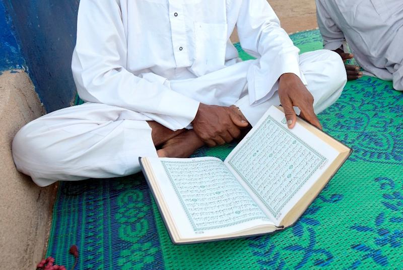 A Muslim cleric reads the Koran outside a mosque on June 19, 2015, during the holy month of Ramadan