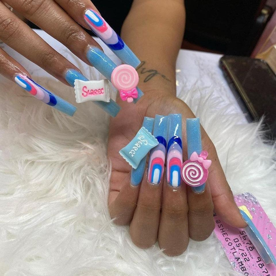 """Nails with large 3D decals have been having a moment on Instagram, and this pretty, blue, extra-long manicure from <a href=""""https://www.instagram.com/SheGotLamboed/"""" rel=""""nofollow noopener"""" target=""""_blank"""" data-ylk=""""slk:SheGotLamboed"""" class=""""link rapid-noclick-resp"""">SheGotLamboed</a> is great nail inspiration. She created a baby-blue base, and on two nails added a lollipop and candy decal. The other two nails have a few curved lines in navy, white, hot pink, blush, and slate-blue shades."""