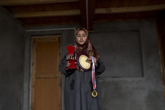 In this Dec. 26, 2018, photo, Bazila Bilal shows the trophies and medals of her brother Saqib Bilal Sheikh inside her home in Hajin village, north of Srinagar, Indian controlled Kashmir. Saqib, who was then 16-years-old, and another teenager walked away from a local soccer pitch in the Kashmiri town of Hajin on a hot day in August, only to return home months later in body bags. The boys journeyed together from playfield to armed rebellion, joining a nearly three-decade insurgency that is drawing greater numbers of teenage boys and young men as New Delhi cracks down on anti-India protests. (AP Photo/ Dar Yasin)