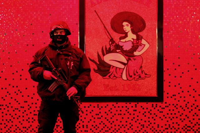 <p>A Federal Police officer guards outside a bar during a special operation at the Zona Norte area in Tijuana, Mexico, Friday, June 12, 2009. Federal Police officers ran an operation looking for drugs, weapons and illegal prostitution, archival inkjet print, 2008-2012. (© Guillermo Arias, courtesy of the artist/Museum of Photographic Arts, San Diego) </p>