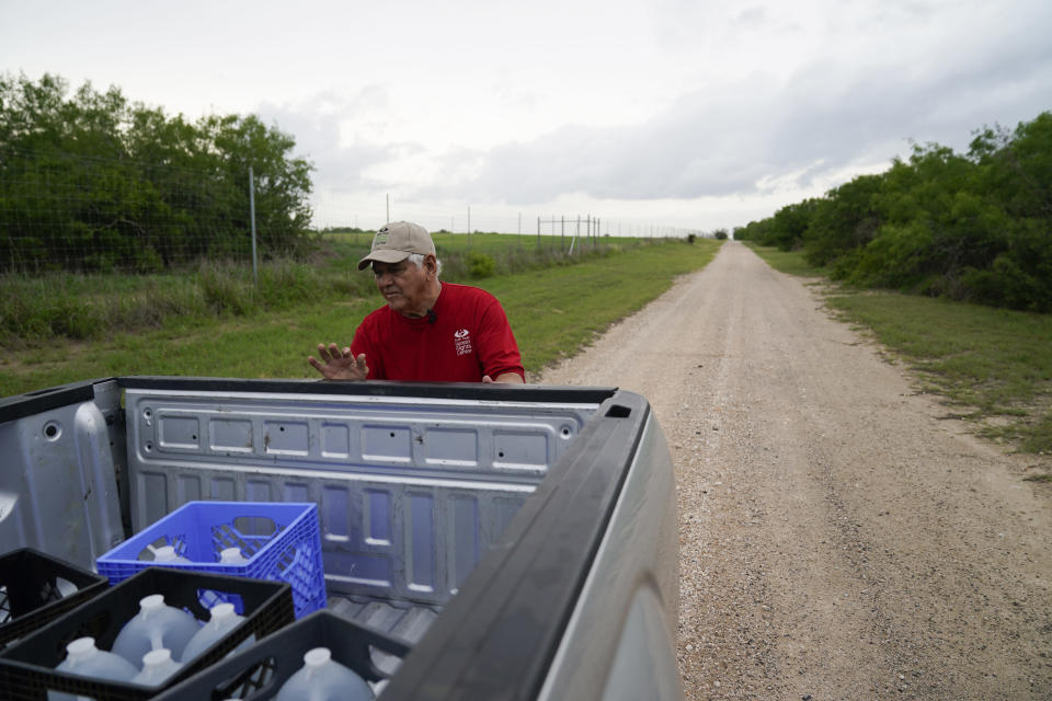 Migrant rights activist Eduardo Canales unloads jugs of water for a water drop Saturday, May 15, 2021, in Falfurrias, Texas. Every week, Canales fills up blue water drums that are spread throughout a vast valley of Texas ranchlands and brush. They are there for migrants who venture into the rough terrain to avoid being caught and sent back to Mexico. (AP Photo/Gregory Bull)