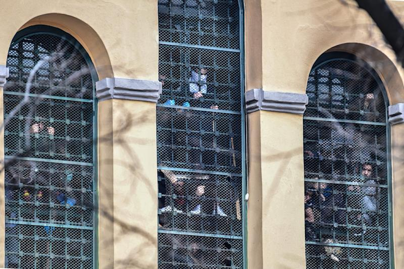 Inmates hang on to bars behind windows of a wing as they stage a protest at the San Vittore prison in Milan on March 9, 2020, in one of Italy's quarantine red zones. - Inmates in four Italian prisons have revolted over new rules introduced to contain the coronavirus outbreak, leaving one prisoner dead and others injured, a prison rights group said on March 8. Prisoners at jails in Naples Poggioreale in the south, Modena in the north, Frosinone in central Italy and at Alexandria in the northwest had all revolted over measures including a ban on family visits, unions said. (Photo by Miguel MEDINA / AFP) (Photo by MIGUEL MEDINA/AFP via Getty Images)