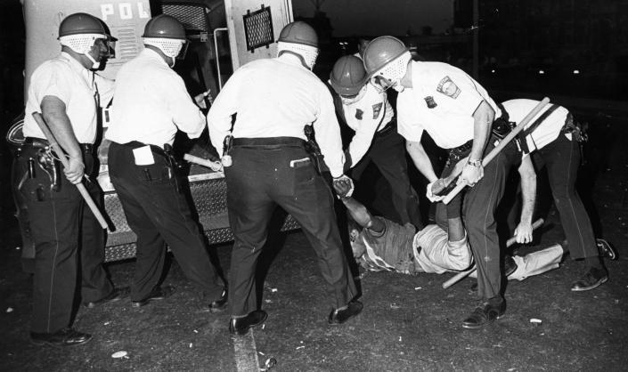 Boston Police officers wearing riot helmets and carrying batons arrest rioters in Roxbury on June 1, 1967. (Bob Dean/The Boston Globe via Getty Images)