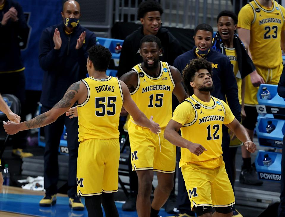 Michigan guards Eli Brooks (55), Chaundee Brown (15) and Mike Smith (12) celebrate during their Sweet 16 game against Florida State.