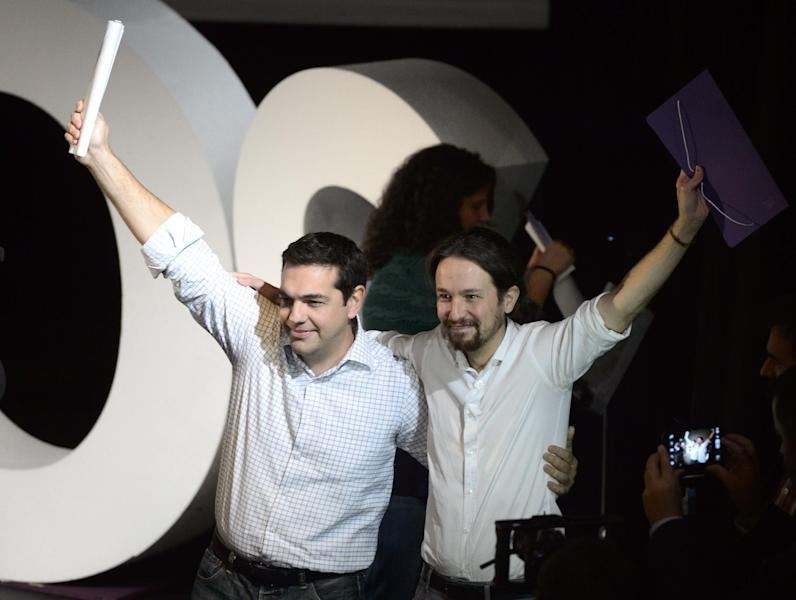 President of Greek oposition SYRIZA, Alexis Tsipras and newly confirmed leader of Podemos, Pablo Iglesias, waving at a party meeting in Madrid on November 15, 2014 (AFP Photo/Dani Pozo)