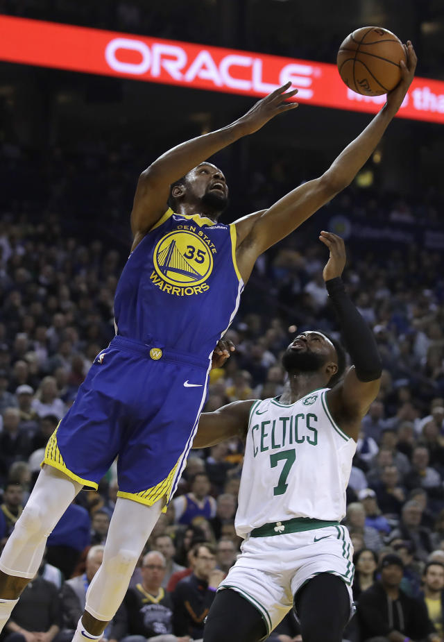 Golden State Warriors' Kevin Durant shoots in front of Boston Celtics' Jaylen Brown (7) during the first half of an NBA basketball game Tuesday, March 5, 2019, in Oakland, Calif. (AP Photo/Ben Margot)