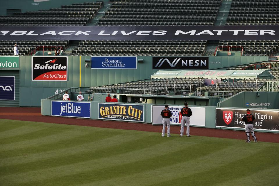 A Black Lives Matter banner is displayed in the bleachers during ceremonies before an opening day baseball game between the Boston Red Sox and the Baltimore Orioles at Fenway Park, Friday, July 24, 2020, in Boston. (AP Photo/Michael Dwyer)