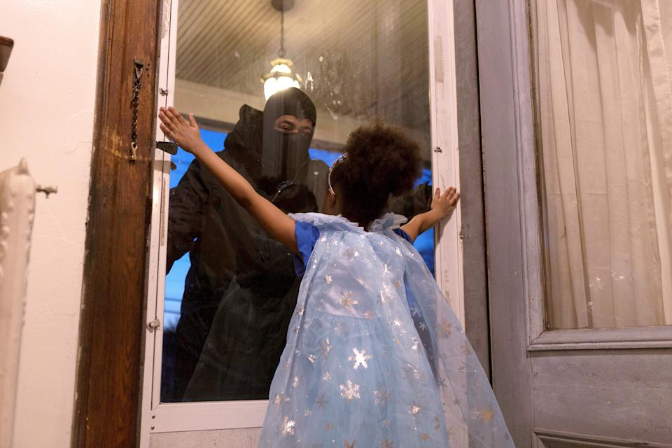 Hashim, an essential worker in the healthcare industry, speaks to his daughter through the closed door as he maintains social distance from his family as he works amid the coronavirus disease (COVID-19) outbreak in New Rochelle, New York, U.S., April 20, 2020. Picture taken April 20, 2020.  REUTERS/Joy Malone     TPX IMAGES OF THE DAY