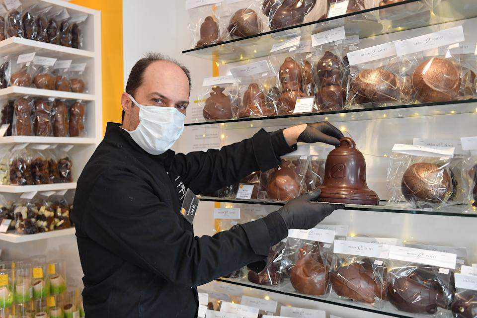 PARIS, FRANCE - APRIL 08: A Man holds an Easter bell in Chocolatier Maison Caffet on Easter week during the coronavirus epidemic (COVID 19) on April 08, 2020 in Paris, France. Many of the traditional Easter activities, including Easter egg hunts, religious processions and Easter Sunday mass, have been canceled as part of measures meant to stem the spread of the coronavirus in France. The country is issuing fines for people caught violating its nationwide lockdown measures intended to stop the spread of COVID-19. The Coronavirus (COVID-19) pandemic has spread to many countries across the world, claiming over 80,000 lives and infecting over 1 million people. (Photo by Stephane Cardinale - Corbis/Corbis via Getty Images)