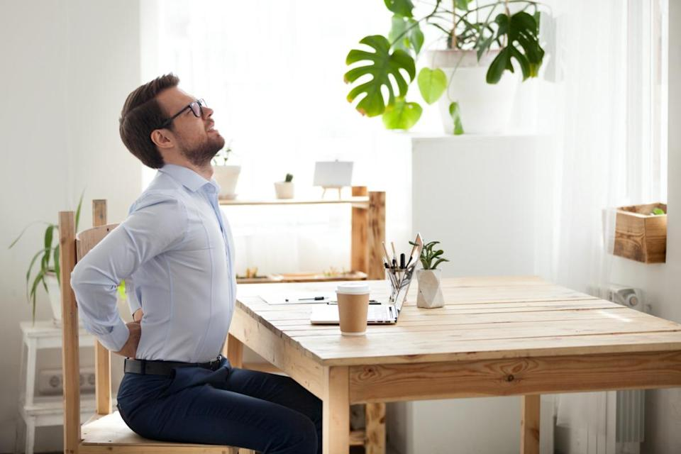 Tired millennial office worker stretch in chair suffer from sitting long in incorrect posture, male employee have back pain or spinal spasm working in uncomfortable position