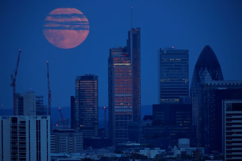 The full moon is seen rising over the City of London financial district in London