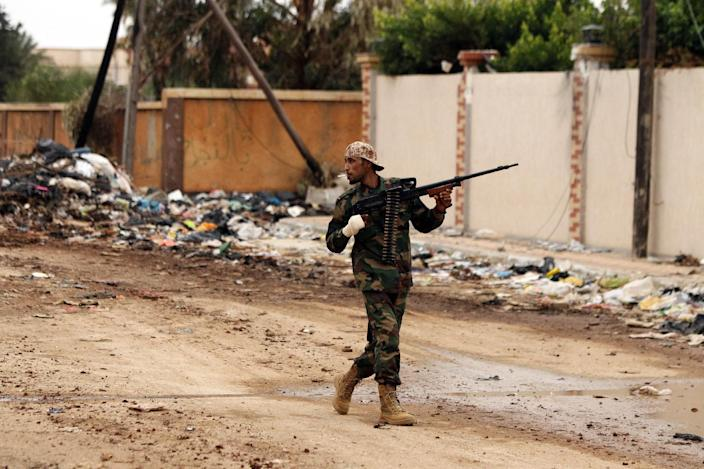 A fighter loyal to Khalifa Haftar walks across a street as he fights alongside the Libyan army in clashes with Islamist gunmen in Benghazi on December 16, 2014 (AFP Photo/Abdullah Doma)
