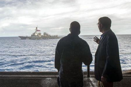 U.S. Secretary of Defense Ash Carter (R) speaks with U.S. Navy Cmdr. Robert C. Francis Jr., as Carter and Malaysian Defense Minister Hishammuddin Hussein (Not Pictured) visited the USS Theodore Roosevelt aircraft carrier in the South China Sea, in this handout photograph taken and released on November 5, 2015. REUTERS/Senior Master Sgt. Adrian Cadiz/Department of Defense/Handout