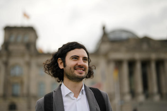 Hakan Demir, grandson of Turkish immigrants, smiled as he poses for a photo during an interview with the Associated Press in front of the German parliament Bundestag building, the Reichstag Building, in Berlin, Tuesday, Sept. 28, 2021. Sunday's national election making Germany's lower house of parliament, or Bundestag, more diverse and inclusive than ever before. For the first time there are also two transgender women, at least three people of African descent and, after years of stagnation, the number of female lawmakers has gone up again as well. (AP Photo/Markus Schreiber)