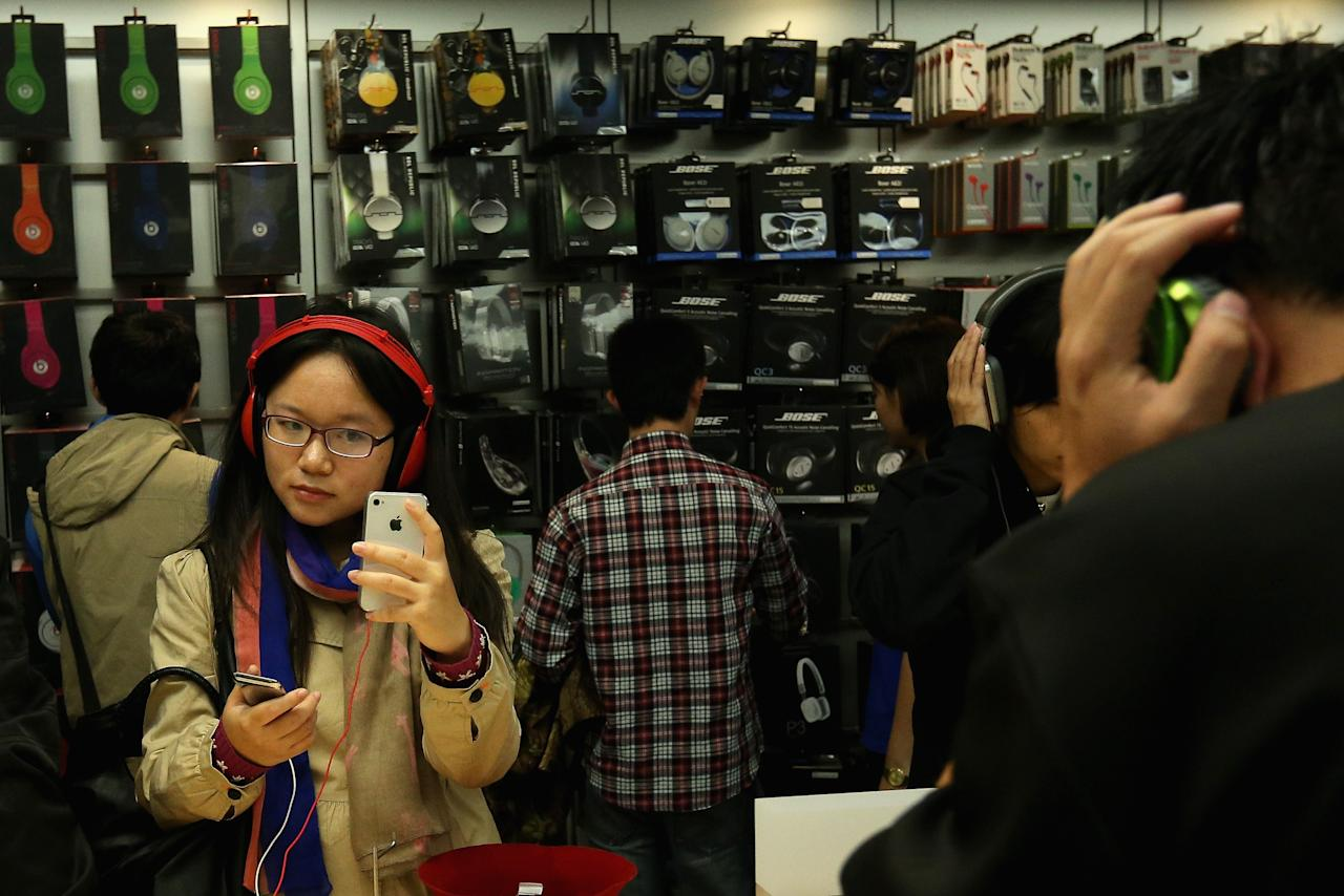 BEIJING, CHINA - OCTOBER 20:  Chinese customers look at iPhone 4S in the newly opened Apple Store in Wangfujing shopping district on October 20, 2012 in Beijing, China. Apple Inc. opened its sixth retail store on the Chinese mainland Saturday. The new Wangfujing store is Apple's largest retail store in Asia.  (Photo by Feng Li/Getty Images)