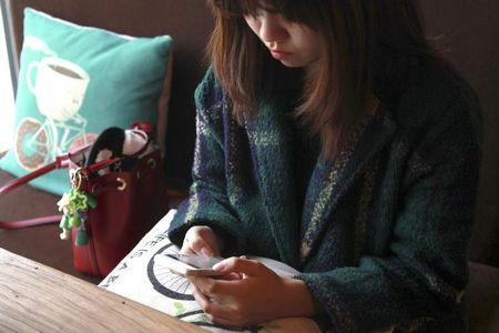 A woman uses an app on a mobile phone at a cafe in Beijing