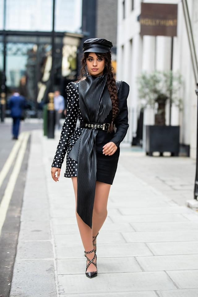 """<p>Camila Cabello wore a black belted dress by Ronald van der Kemp with <a href=""""https://www.popsugar.com/fashion/camila-cabello-perfection-belt-46709320"""" class=""""ga-track"""" data-ga-category=""""Related"""" data-ga-label=""""https://www.popsugar.com/fashion/camila-cabello-perfection-belt-46709320"""" data-ga-action=""""In-Line Links"""">a belt that had """"perfection""""</a> written on it while in London. </p>"""