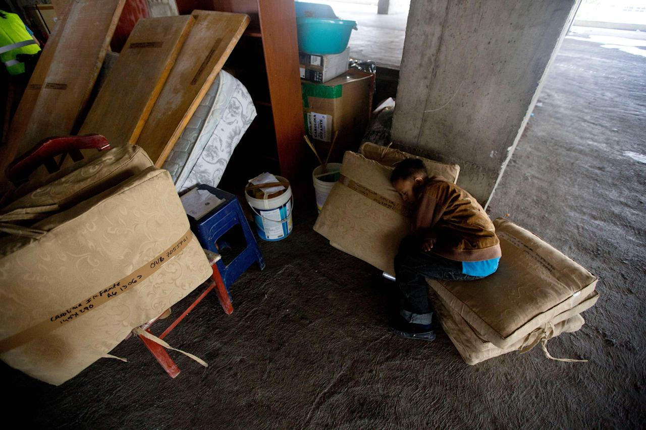 A boy sleeps on his family's belongings as he waits for a truck outside the world's tallest slum, the Tower of David, a half-built skyscraper that was abandoned in the 1990s and was transformed by squatters into a vertical ghetto, in Caracas, Venezuela, Tuesday, July 22, 2014. Officials and armed soldiers began moving out the first of thousands of squatters who have lived for nearly a decade in a soaring, half-built skyscraper in the heart of Caracas. (AP Photo/Fernando Llano)