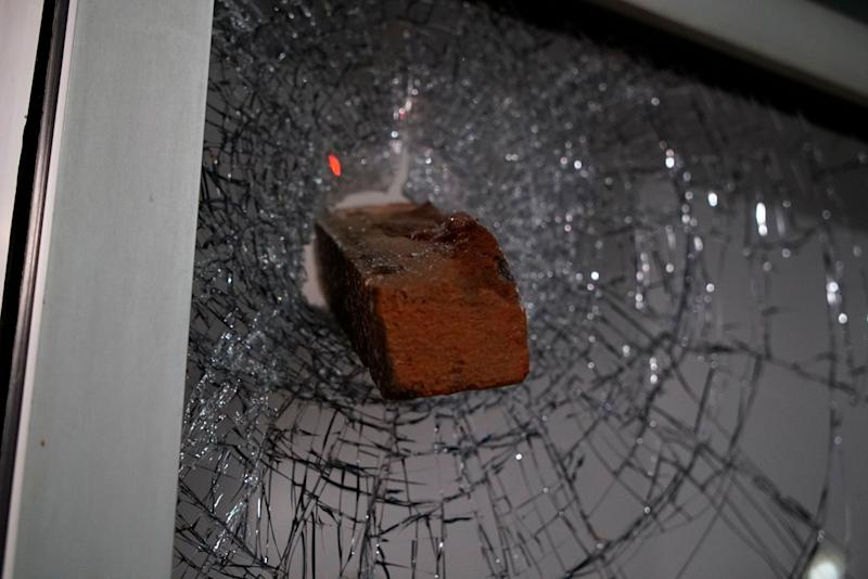 A brick protrudes from a shattered window in downtown Raleigh, N.C., on Monday, June 1, 2020. It was the second day of protests in the North Carolina capital following the death of Minnesotan George Floyd while in police custody. (AP Photo/Allen G. Breed)