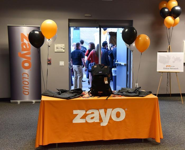 Desk with Zayo logo and orange and black balloons, with a huddle of people in background.