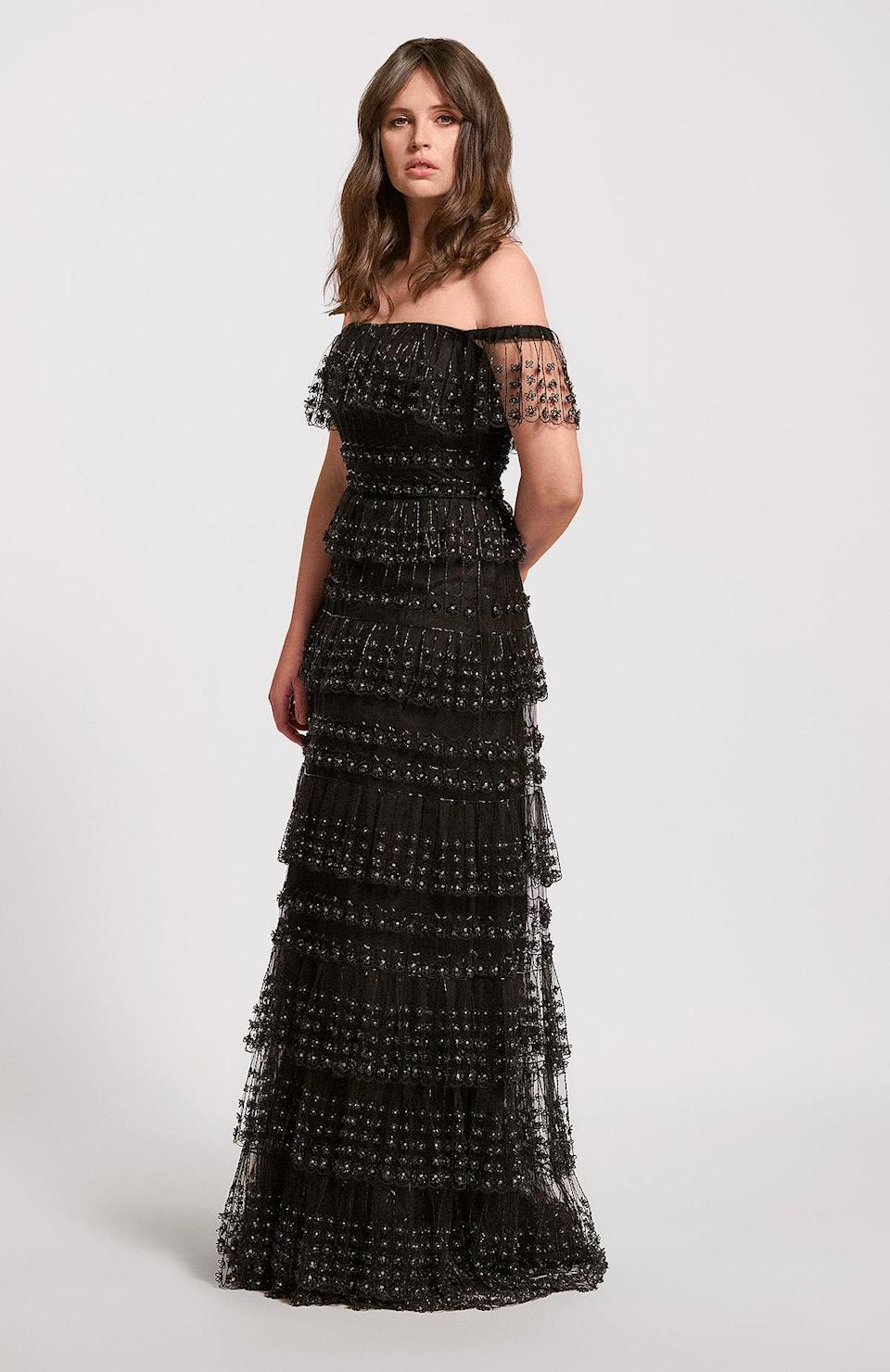 <p>wears an off-the-shoulder tiered Valentino gown with all-over embellishments, paired with Cartier jewels. </p>