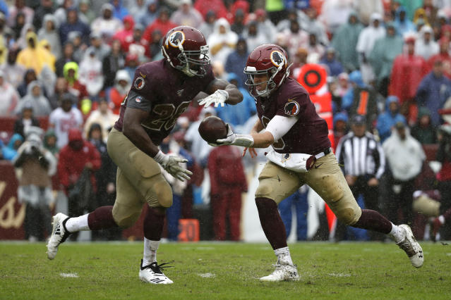 Washington Redskins quarterback Case Keenum, right, hands off to Washington Redskins running back Adrian Peterson in the second half of an NFL football game against the San Francisco 49ers, Sunday, Oct. 20, 2019, in Landover, Md. (AP Photo/Alex Brandon)