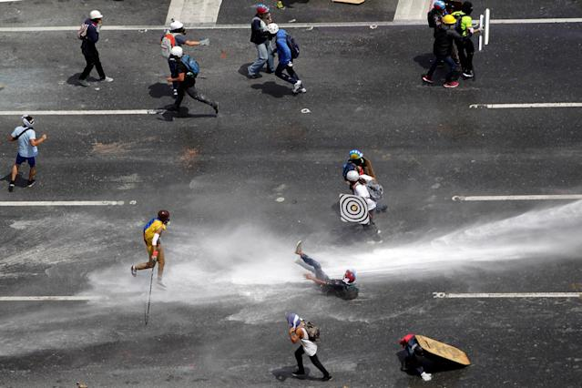 <p>A demonstrator is hit by a jet of water during a rally against Venezuela's President Nicolas Maduro in Caracas, Venezuela, May 26, 2017. (Christian Veron/Reuters) </p>