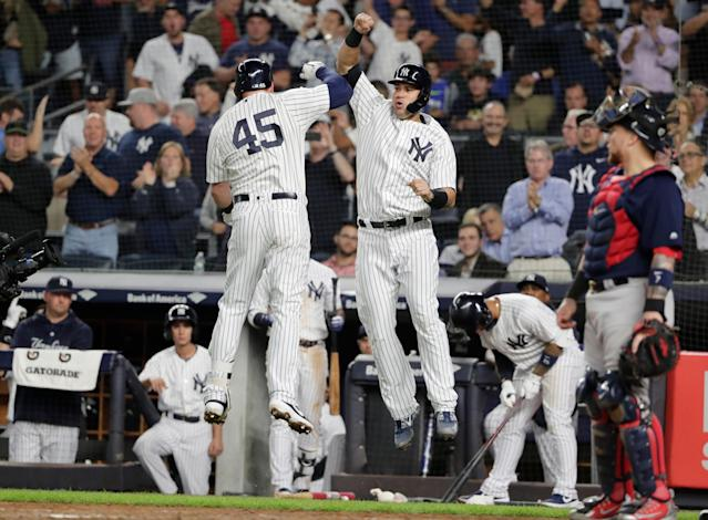Boston Red Sox catcher Christian Vazquez, right, watches as New York Yankees' Luke Voit, left, celebrates with Gary Sanchez after Voit hit a two-run home run during the second inning of a baseball game Thursday, Sept. 20, 2018, in New York. (AP Photo/Frank Franklin II)