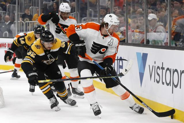 Boston Bruins' Sean Kuraly (52) battles Philadelphia Flyers' Kevin Hayes (13) for the puck during the first period of an NHL hockey game in Boston, Sunday, Nov. 10, 2019. (AP Photo/Michael Dwyer)