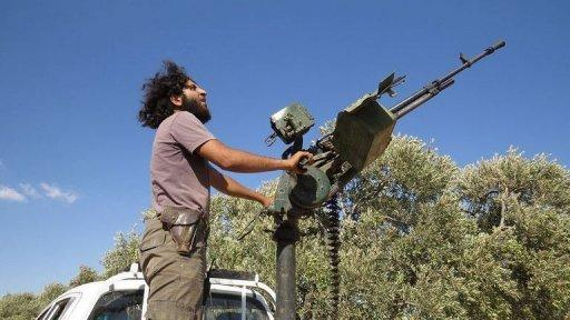 <p>A rebel fighter fires a heavy machine gun mounted on the back of a pick-up truck during a battle with Syrian government forces in the rebel-held northwestern Syrian province of Idlib on September 9, 2013.</p>